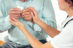 Doctor de sexo femenino que celebra las manos mayores de los pacientes en la oficina médica Foto de archivo