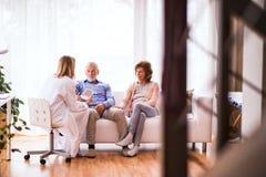 Doctor de sexo femenino que comprueba la presión arterial del hombre mayor Foto de archivo libre de regalías