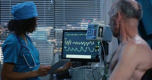 Doctor de sexo femenino que comprueba ritmo cardíaco de los pacientes almacen de metraje de vídeo
