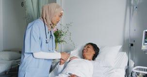 Doctor de sexo femenino que conforta al paciente que miente en la cama de hospital 4k almacen de video