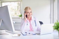 Doctor de sexo femenino que consulta con su paciente en el teléfono móvil fotos de archivo libres de regalías