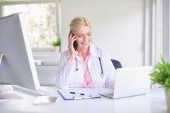 Doctor de sexo femenino que consulta con su paciente en el teléfono móvil foto de archivo libre de regalías