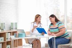 Doctor de sexo femenino que consulta a la mujer gorda foto de archivo