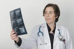 Doctor de sexo femenino que examina exactamente una radiografía foto de archivo libre de regalías