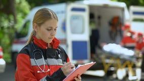 Doctor de sexo femenino que guarda los informes médicos, equipo de la ambulancia que pone el ensanchador abajo metrajes