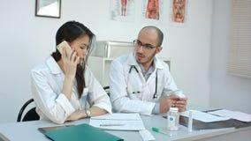 Doctor de sexo femenino que habla en el teléfono que pide a su compañero de trabajo masculino consejo fotos de archivo libres de regalías
