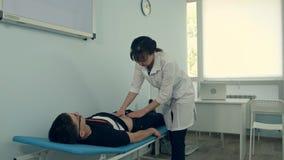 Doctor de sexo femenino que hace el examen abdominal en el paciente masculino foto de archivo libre de regalías