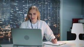 Doctor de sexo femenino que hace llamada video en línea con el paciente en el ordenador y que da recomendaciones almacen de metraje de vídeo
