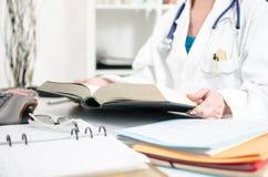 Doctor de sexo femenino que lee un libro médico Imagen de archivo