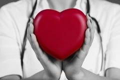 Doctor de sexo femenino que lleva a cabo el corazón rojo imagenes de archivo