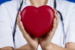 Doctor de sexo femenino que lleva a cabo el corazón rojo Foto de archivo