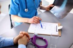 Doctor de sexo femenino que lleva a cabo el formulario de inscripción mientras que Imagenes de archivo