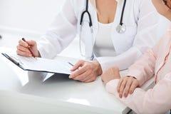 Doctor de sexo femenino que lleva a cabo el formulario de inscripción mientras que consulta al paciente en el hospital imagenes de archivo
