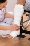 Doctor de sexo femenino que lleva a cabo la pierna del paciente Imagen de archivo