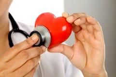 Doctor de sexo femenino que lleva a cabo una forma roja del corazón Foto de archivo libre de regalías