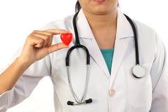 Doctor de sexo femenino que lleva a cabo una forma roja hermosa del corazón Fotos de archivo libres de regalías