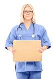 Doctor de sexo femenino que lleva a cabo una muestra en blanco del cartón Foto de archivo libre de regalías