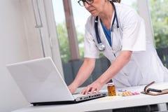 Doctor de sexo femenino que mecanografía en el ordenador portátil Imagenes de archivo