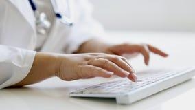 Doctor de sexo femenino que mecanografía en el teclado en la oficina almacen de video