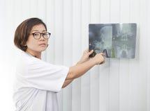 Doctor de sexo femenino que mira en la película de radiografía principal del cráneo Imágenes de archivo libres de regalías