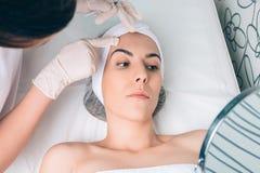 Doctor de sexo femenino que muestra al paciente que la cara divide en zonas Imagen de archivo