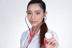 Doctor de sexo femenino que muestra el estetoscopio para el chequeo sobre el backgro blanco Foto de archivo