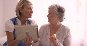 Doctor de sexo femenino que muestra informe médico a la mujer mayor en la tableta digital almacen de metraje de vídeo