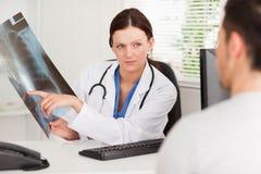 Doctor de sexo femenino que muestra la radiografía paciente Fotos de archivo libres de regalías