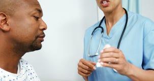 Doctor de sexo femenino que muestra a un paciente asmático cómo utilizar un inhalador del asma metrajes