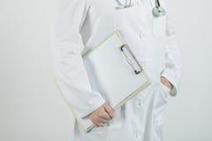 Doctor de sexo femenino que presenta con la libreta del tablero y el papel en blanco Fotografía de archivo