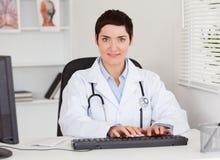 Doctor de sexo femenino que pulsa con su ordenador Foto de archivo