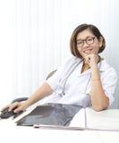 Doctor de sexo femenino que se sienta en su sitio de funcionamiento con la cara sonriente Fotos de archivo libres de regalías