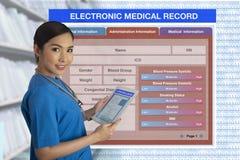 Doctor de sexo femenino que sostiene la tableta con recor médico electrónico del espacio en blanco fotos de archivo