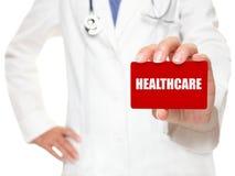 Doctor de sexo femenino que sostiene la tarjeta de la ATENCIÓN SANITARIA Imagen de archivo