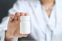 Doctor de sexo femenino que sostiene y que muestra la botella de la medicina imagen de archivo