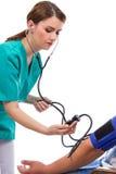 Doctor de sexo femenino que toma la presión arterial Foto de archivo libre de regalías