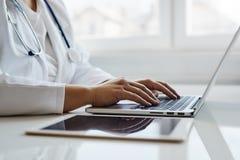 Doctor de sexo femenino que trabaja con su computadora portátil imagen de archivo