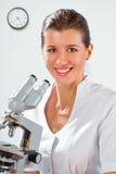 Doctor de sexo femenino que trabaja con un microscopio Imagen de archivo