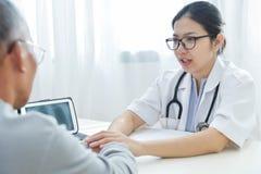 Doctor de sexo femenino que tranquiliza al paciente masculino mayor Fotografía de archivo