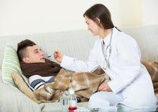 Doctor de sexo femenino que trata al adolescente con el jarabe en casa Foto de archivo