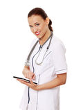 Doctor de sexo femenino que usa el ordenador de la tablilla. Imagenes de archivo
