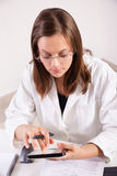 Doctor de sexo femenino que usa la tableta digital en oficina Fotos de archivo
