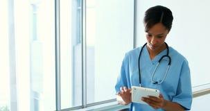 Doctor de sexo femenino que usa la tableta digital en pasillo almacen de metraje de vídeo