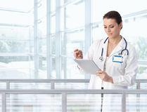 Doctor de sexo femenino que usa la tablilla en hospital imagenes de archivo