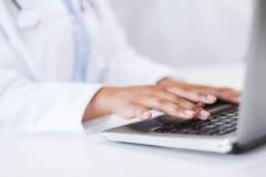 Doctor de sexo femenino que usa su ordenador portátil Fotografía de archivo libre de regalías