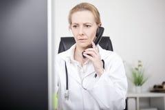 Doctor de sexo femenino serio en el teléfono que mira el monitor Fotografía de archivo