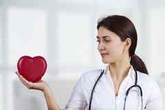 Doctor de sexo femenino sonriente con el corazón y el estetoscopio rojos foto de archivo libre de regalías