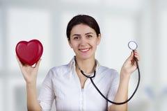 Doctor de sexo femenino sonriente con el corazón y el estetoscopio rojos imágenes de archivo libres de regalías