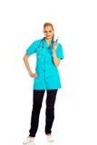 Doctor de sexo femenino sonriente con el estetoscopio que sostiene el termómetro Fotografía de archivo