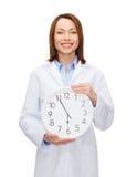 Doctor de sexo femenino sonriente con el reloj de pared Fotos de archivo